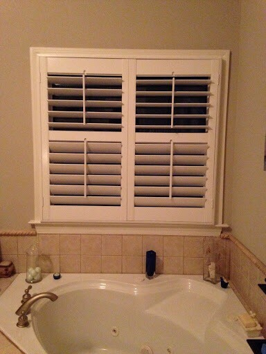 plantation wood shutters over a tub in a master bathroom